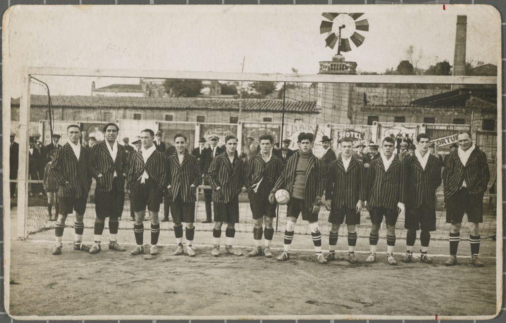 Retrat de grup de l'equip de futbol de la Unió Deportiva Girona amb uniforme davant d'una porteria del camp de futbol de Vista Alegre de Girona. S'identifica a Viñas, Poch, Weis, Santamaria, Feliu, Bosch, Gauchia, Colls, Carrera, Pons i Stamper.